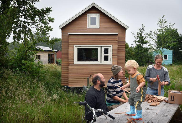 Den Haag: op het complex voor tiny houses hakt Jente de Vries houtjes bij haar huisje. Buurtgenoten Jurre Antonisse, Jasmijn Twilt en hun kind Ole zijn op bezoek. Beeld Marcel van den Bergh