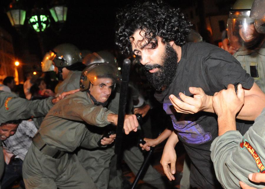 De oproepolitie in gevecht met een van de demonstranten, Rabat, vrijdagavond.