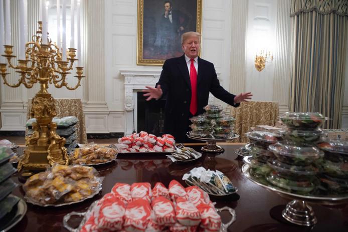 De Amerikaanse president voor een tafel met het bestelde eten.