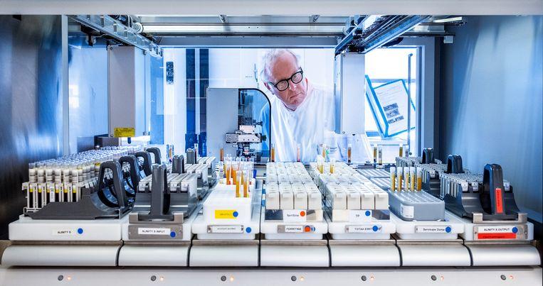 Hans Zaaijer van bloedbank Sanquin bij een van de machines die antistoffen in het bloed moeten ontdekken. Beeld Raymond Rutting / de Volkskrant