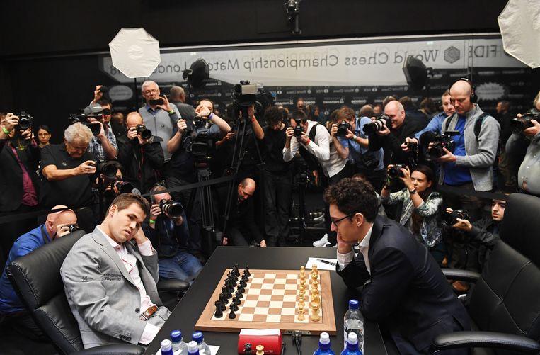 Carlsen (links) tegenover zijn uitdager Caruana, tijdens het wereldkampioenschap schaken in Londen. 26 november 2018. Beeld EPA