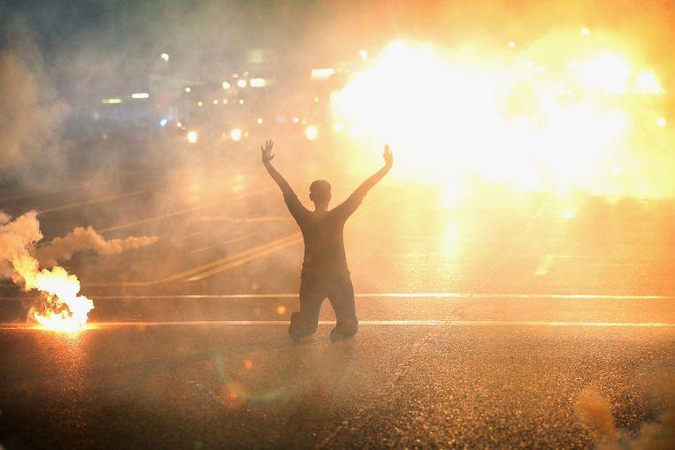 Een vrouw zit op haar knieën op straat met haar handen in de lucht. In de lucht hangt traangas. Beeld afp