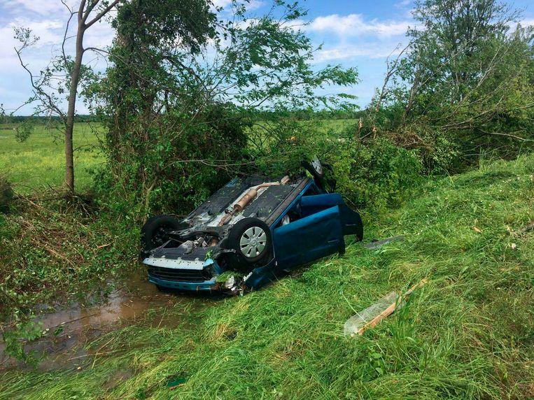 Een auto ligt op z'n kop in de sloot in Franklin, Texas, na de doortocht van wat mogelijk een tornado was.