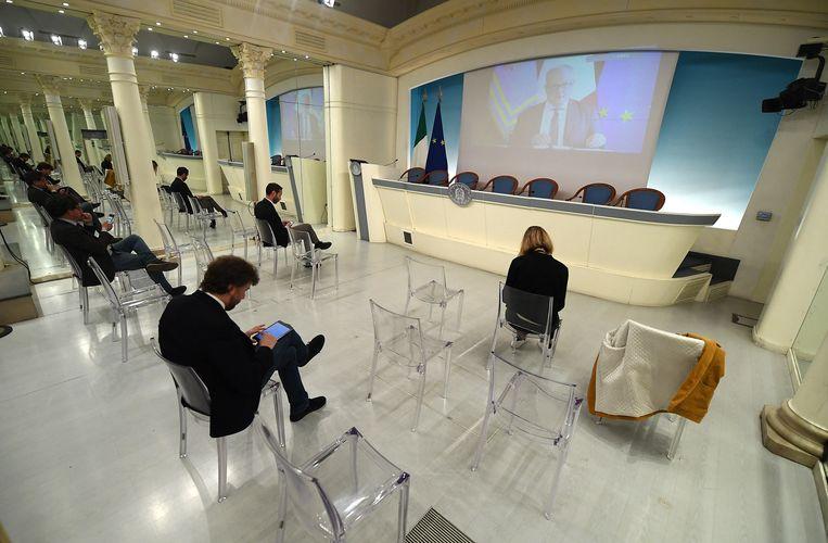 Tijdens een video persconferentie spreekt de Italiaanse minister van Economie en Financiën een klein publiek toe.  Beeld EPA