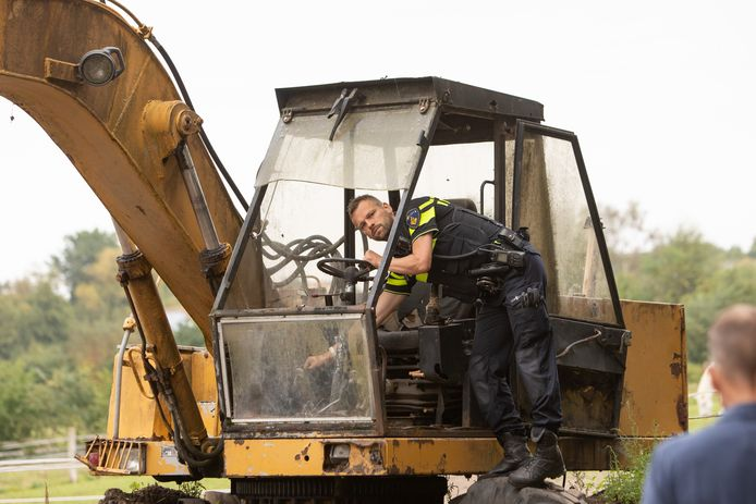 De politie haalt onder meer een graafmachine weg.