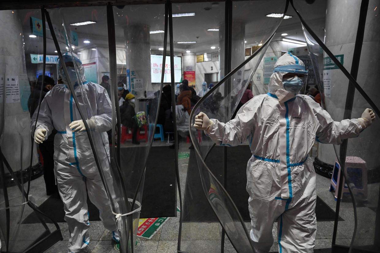 Het medisch personeel is helemaal ingepakt in een ziekenhuis in Wuhan. Artsen en verplegers moeten 24 uur aan een stuk werken. © AFP