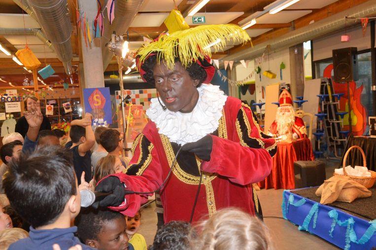 Sinterklaas (achteraan) luistert hoe de kinderen liedjes zingen samen met Zwarte Piet.