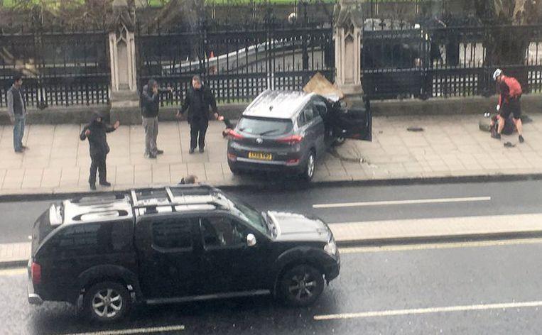 Een verongelukte auto en gewonden in Bridge Street vlak bij het Britse parlement in Londen. Beeld AP