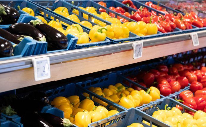 Aubergines en gele en rode paprika's in de supermarkt.