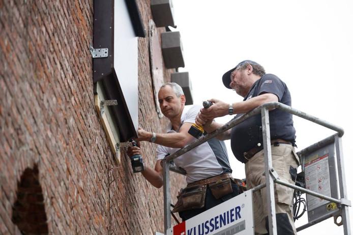 Kees de Jong (r) hangt samen met Frits Hommel tegenover de brandweerkazerne van Nieuw-Vossemeer een aantal kastjes voor vleermuizen en gierzwaluwen op. foto Marcel Otterspeer/Pix4Profs
