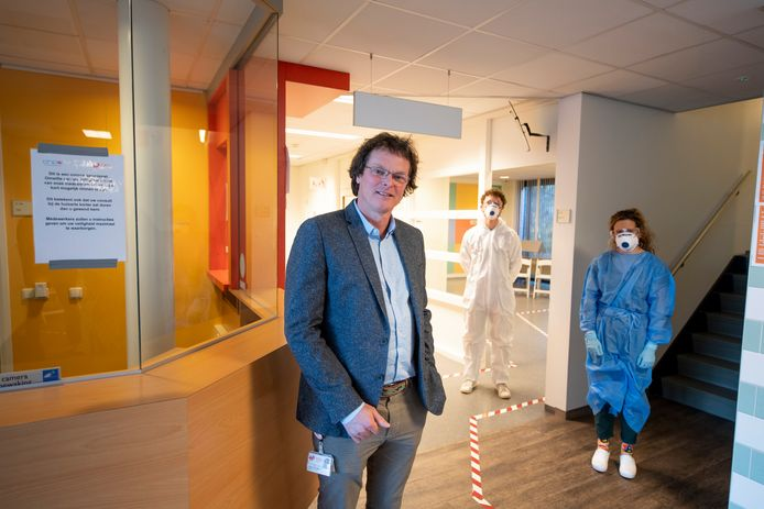 Directeur Luc de Vries in de coronapost in Hengelo, die donderdagavond in gebruik wordt genomen. Op de achtergrond twee co-assistenten in beschermende kleding.