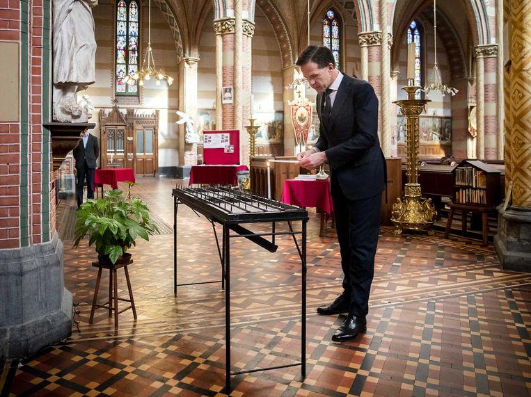 Premier Mark Rutte steekt een kaars aan in de Sint Jacobsker in Den Haag. Hij besprak met vertegenwoordigers van de katholieke gemeenschap hoe zij omgaan met het coronavirus. Beeld EPA