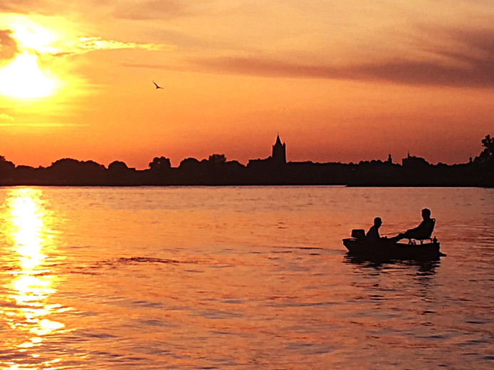 De rivier, een bootje en in de verte zicht op de toren van Gorinchem. Een zomeravond op het Woerkums strandje.