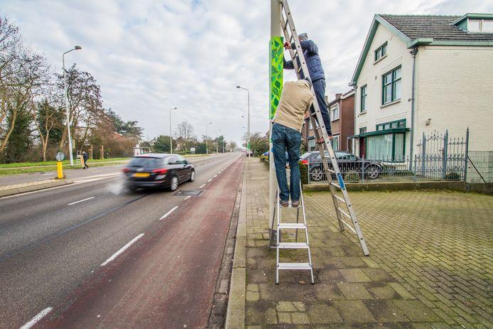 Bewoners hangen groene plakkaten op aan de Graafseweg