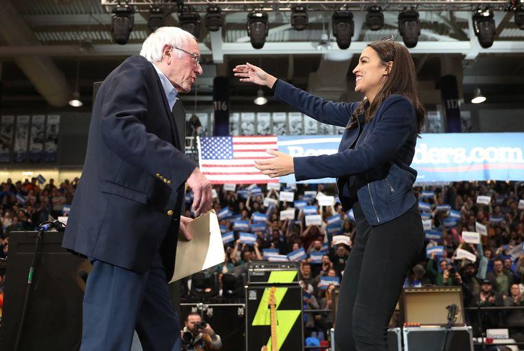 Alexandria Ocasio-Cortez en Bernie Sanders ontmoeten elkaar bij een campagne bijeenkomst van Sanders. Beeld AFP