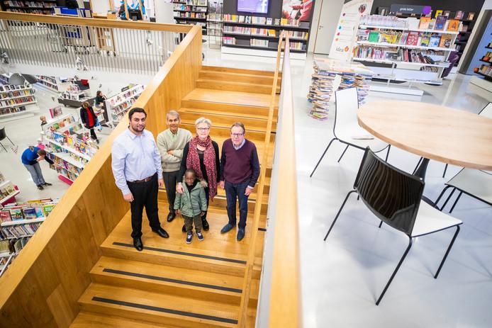 Van links naar rechts poseren in cultuurhuis Het Lichtruim in Bilthoven: Saber Alizai, Kabir Roy Chowdhury, Hanneke Eilers en Adri Peters.  Voor hen staat Raphael (5), die een paar weken geleden in het kader van gezinshereniging in De Bilt is gekomen.