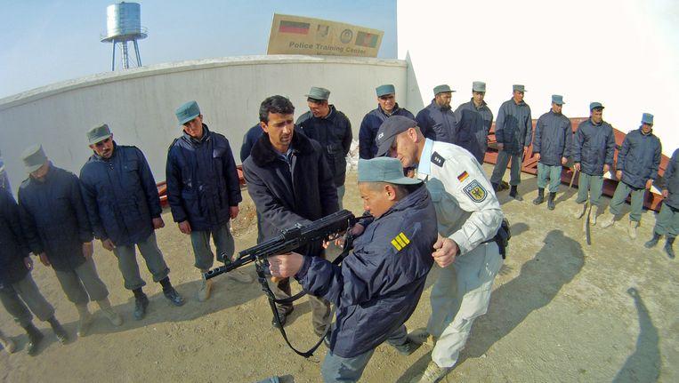 Een Duitse politieman traint Afghaanse politiemensen in opleiding in het police trainingscentre in Kunduz. Beeld ANP