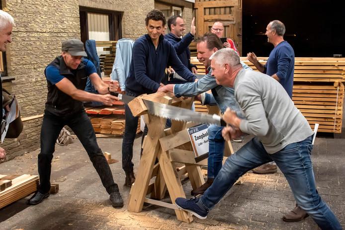 Zij gaan helemaal los in Gilze met de grote Gils Kwist. Foto bij zagerij De Beuk waar teams elkaar bestrijden in het doorzagen van een balk.