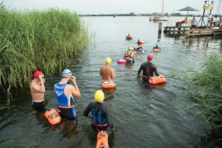 Portemonnees en iPhones verdwijnen in opblaasbare drijfzakken die de zwemmers om hun middel dragen. Beeld Sander Nieuwenhuys