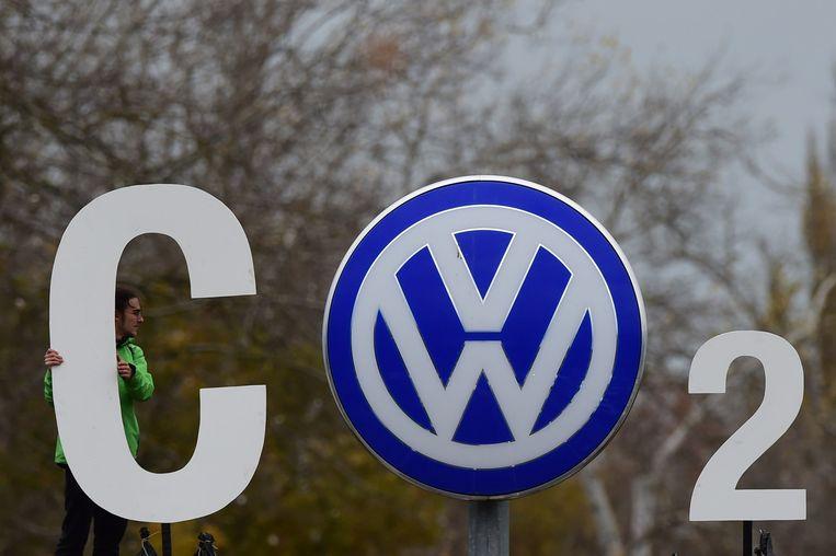 Greenpeace-demonstrant bij een Volkswagen-embleem. Beeld afp