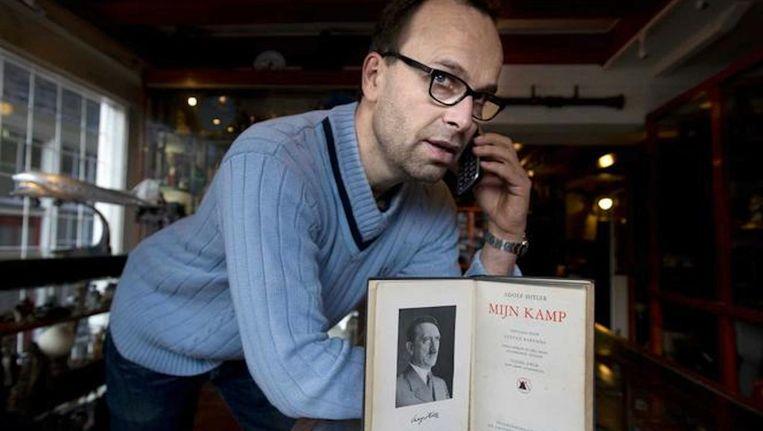 Galeriehouder Michiel van Eyck met een Nederlands exemplaar van Mein Kampf. Beeld ANP