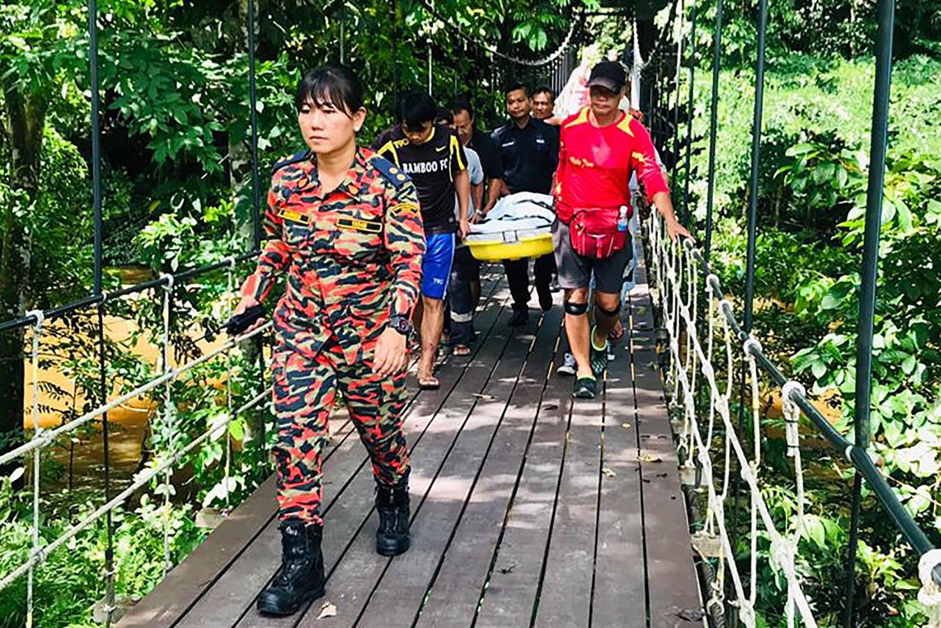 Hulpverleners dragen een lichaam uit de grot in het Mulu-park.