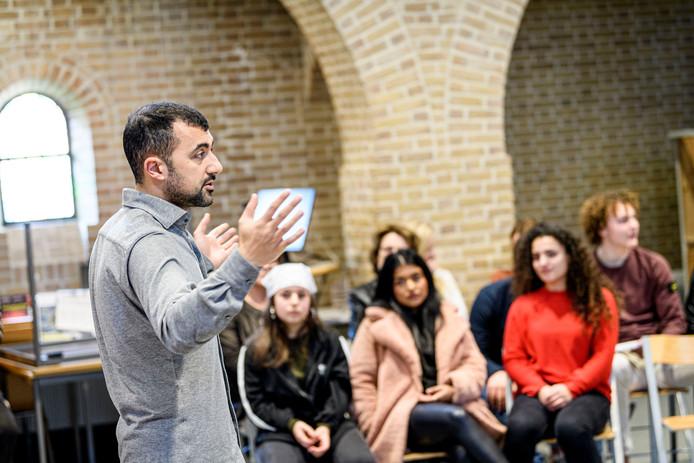 Özcan Akyol in een les Leesbevordering. In de Mediatheek gaat hij met leerlingen van de Grundel in gesprek.