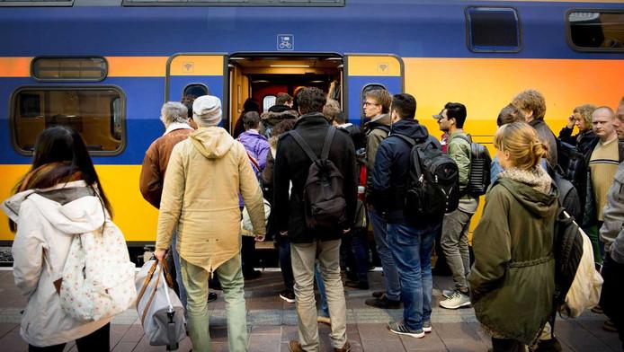 Reizigers stappen op de trein op Rotterdam Centraal. ConsumentenClaim gaat namens ontevreden reizigers een claim indienen tegen de Nederlandse Spoorwegen.