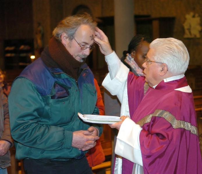 Een Tilburgse pastoor deelt een askruisje uit.