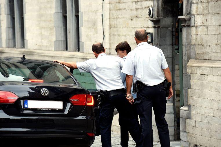 De beklaagde wordt onder politiebegeleiding naar de raadkamer gebracht.