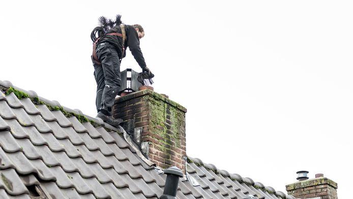 Jordy van Velzen veegt een schoorsteen. Daartoe heeft hij borstels tot zijn beschikking.