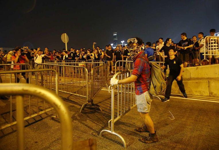 De betogers halen op hun beurt de dranghekken weer weg. Beeld reuters