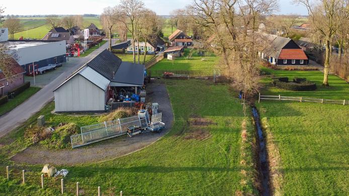 De situatie aan de Sluitersweg in Rouveen, met links het perceel van Lucas Knoll en rechts het huis, met uitbouw met rode dakpannen, van de familie Timmerman. Knoll is overigens zelf (iets rechts van midden) bezig met werkzaamheden aan een hek.
