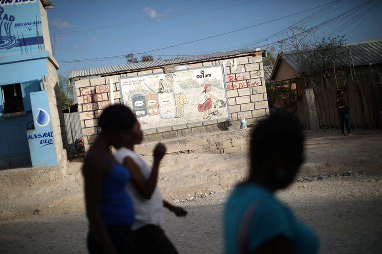 Vrouwen passeren een poster van Oxfam in de hoofdstad van Haïti.  Beeld Reuters
