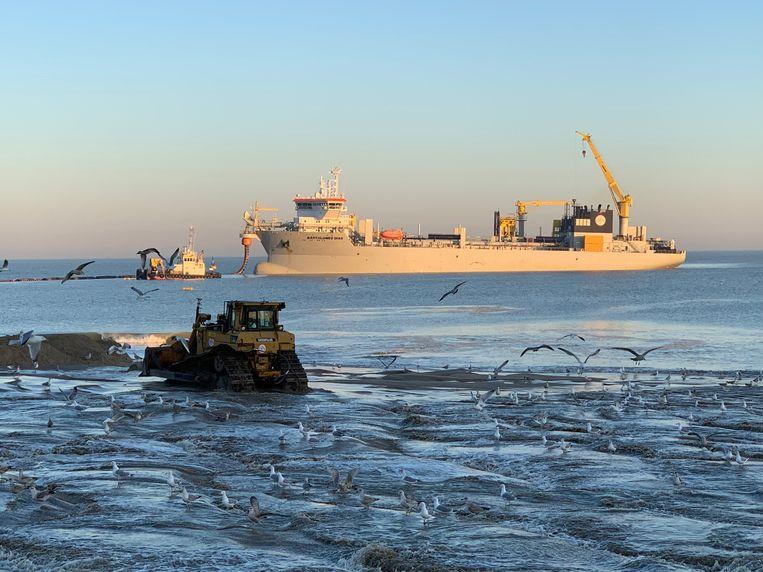 Het zand wordt via persleidingen op het strand gespoten. Bulldozers nivelleren daarna de opgespoten zandhopen.