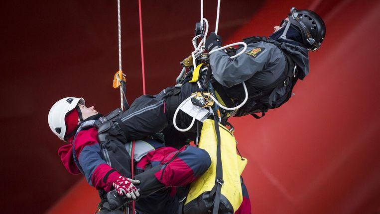Een Greenpeace-activiste wordt door de politie van het platform Transocean Spitsbergen gehaald.