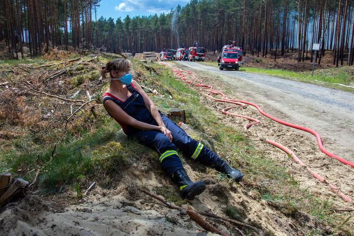 Een vermoeide brandweervrouw neemt rust na het blussen van de enorme bosbrand in Mecklenburg-Vorpommern.