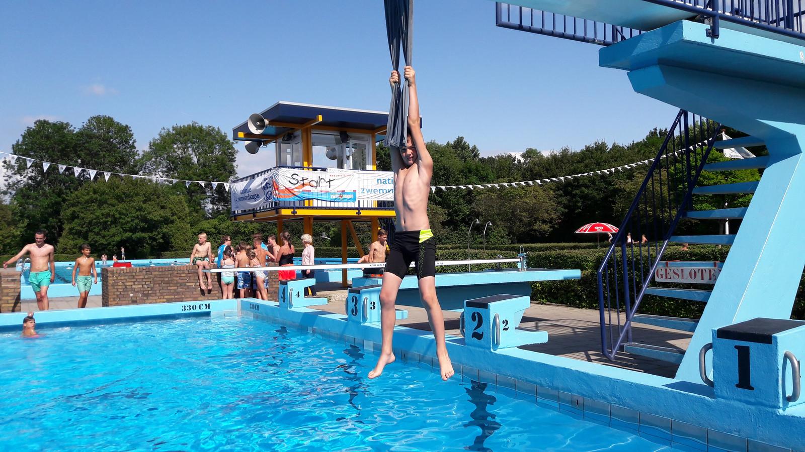 Arco Houtman doet een poging om zijn record spijkerbroekhangen te verbeteren tijdens de spelletjesmiddag in zwembad Den Inkel.