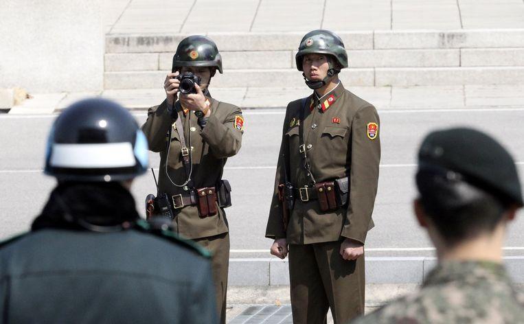 De fotograferende militairen zijn Noord-Koreanen, de twee vooraan zijn Zuid-Koreaanse militairen die het bezoek van minister Tillerson beveiligen. Panmunjom is een dorp in de gedemilitariseerde zone waar in 1953 de wapenstilstand werd getekend. Omdat die nooit is omgezet in een vredesverdrag zijn de twee Korea's formeel nog altijd met elkaar in oorlog.  Beeld REUTERS