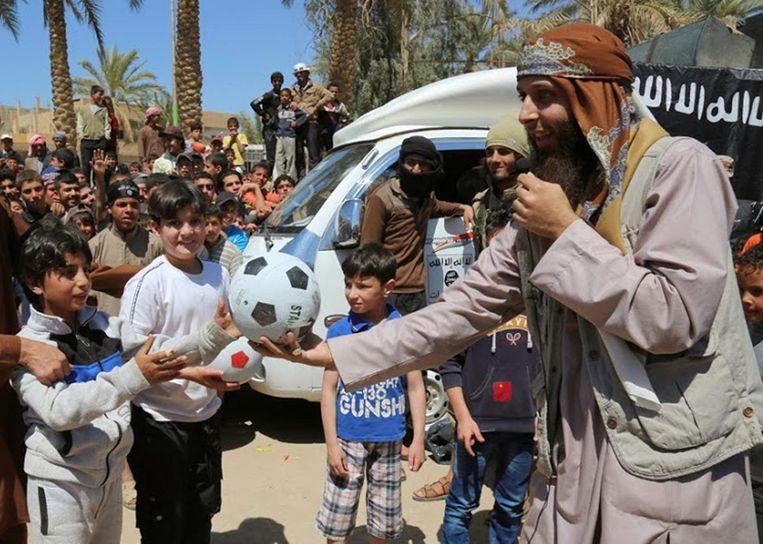Een IS-gelieerde website verspreidde in januari 2015 deze foto waarop een aanhanger van Islamitische Staat in Raqqa voetballen uitdeelt aan kinderen.