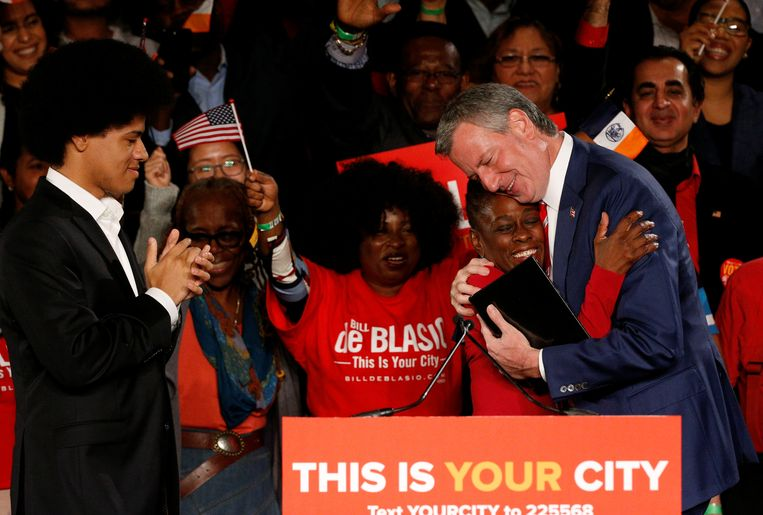 De New Yorkse burgemeester Bill de Blasio omhelst zijn vrouw Chirlane McCray terwijl hun zoon Dante (links) toekijkt.