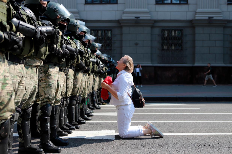 Een vrouw knielt voor de politie die een blokkade heeft opgeworpen tegen de protesten.  Beeld AP