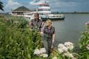 Drimmelen - Angela Knook (l) en Eveliene Jansen van Staatsbosbeheer aan de oevers van de Amer met op achtergrond de toeristische rondvaartboten en de Biesbosch.
