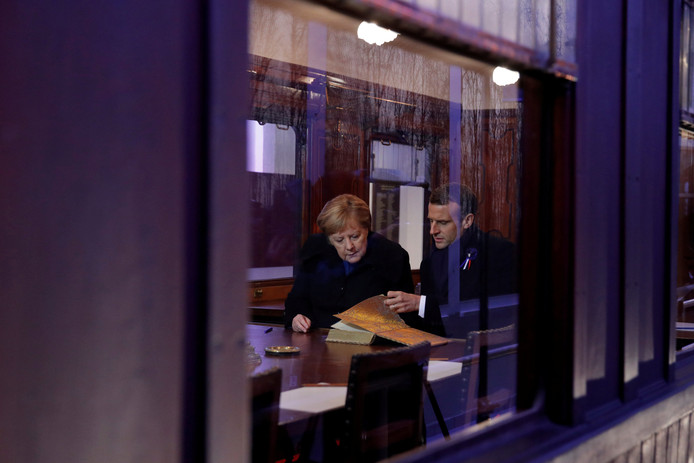 De Franse president Emmanuel Macron en de Duitse Bondskanselier Angela Merkel bekijken een historisch boek in de (kopie) van de treinwagon waar op 11 november 1918 om vijf uur 's morgens de wapenstilstand werd gesloten.
