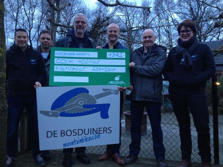 Leden van MTB De Bosduiners schenken de opbrengst aan Rigo Verhaert (3de van l.) van Coda.