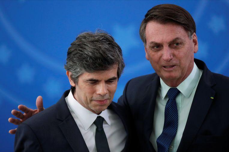 De Braziliaanse President Jair Bolsonaro (rechts) omarmt Nelson Teich tijdens zijn beëdiging op 17 april.  Vrijdagochtend meldde het ministerie van Volksgezondheid dat minister Teich ermee ophoudt. Beeld REUTERS