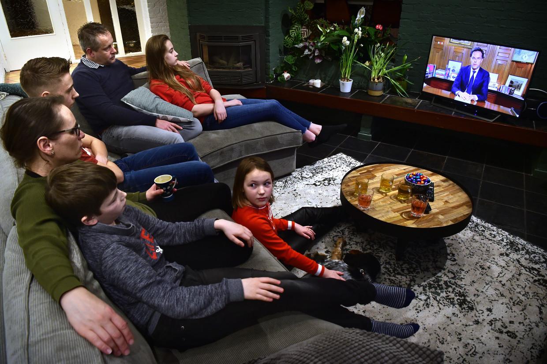 Premier Mark Rutte geeft een toespraak aan het volk via de tv. De familie Weijers- van Capelle luistert samen op de bank.  Beeld null