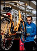Een mecanicien is bezig met een Swapfiets in het magazijn in Amsterdam.