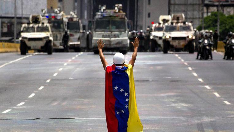 Een demonstrant tegenover een politiemacht tijdens protesten in Venezuela. Beeld afp