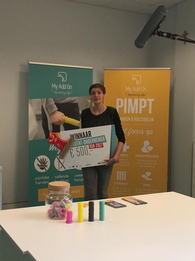 Marie (23) van 'My Add On' ontvangt een cheque van 500 euro van UNIZO. Ze ontwierp kousjes om over handvatten krukken te trekken.